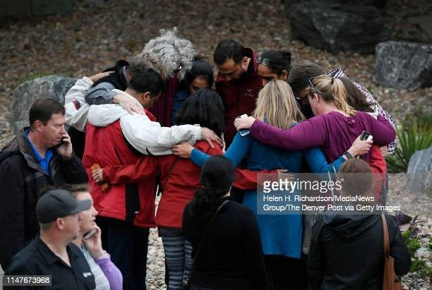 A group hugs one another as they wait outside of the Highlands Ranch Recreation Center at Northridge to pick up their children after a shooting at...