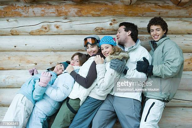Group in winter clothes falling back onto each other, three quarter length, in front of log wall, portrait
