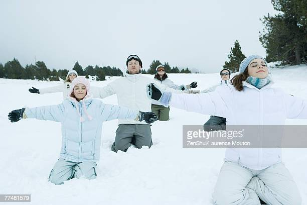 Group kneeling in snow with arms out and eyes closed