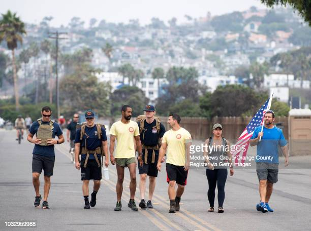 A group led by Marine Major Kalani Creutzburg and Staff Sgt Nate Schoemer in yellow from left walk along Doheny Beach with a female bodybuilder...