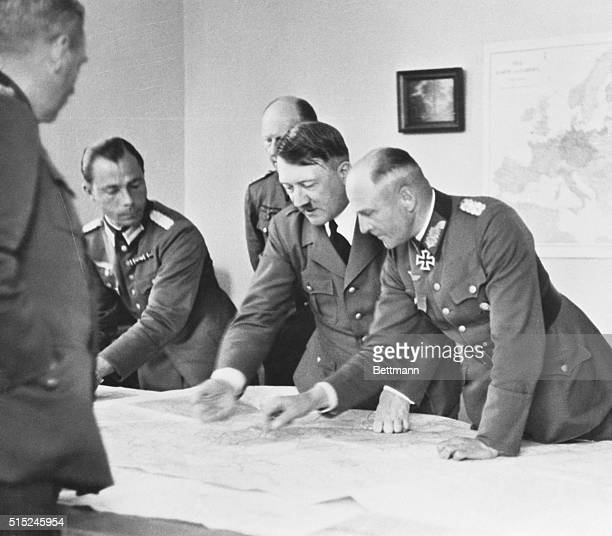 Group Looking over War Maps. Berlin, Germany: Left to right: Major Deile, Adolf Hitler, General Jodl, Admiral Raeder; extreme left, facing table, is...