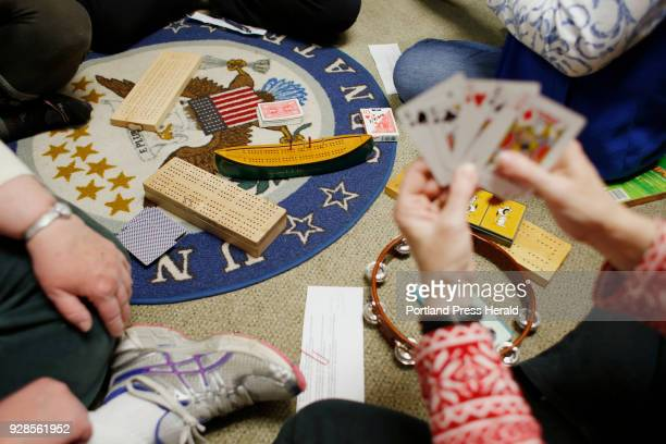 A group made of mostly Peaks Island residents participate in a CribbageIn at Sen Susan Collins' Portland office on Friday Dec 15 as they encourage...