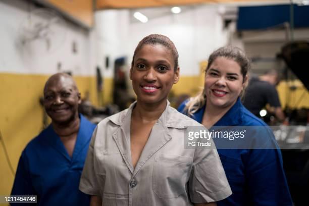 mujeres mecánicas de grupo en reparación de automóviles - equidad de genero fotografías e imágenes de stock