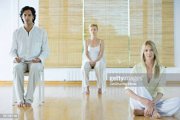Group meditation, adults sitting in different positions