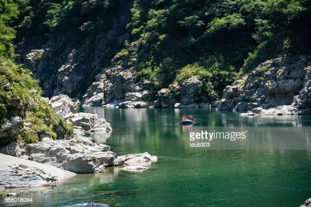 グループの男性と女性の穏やかな川でラフティング - ラフティング ストックフォトと画像