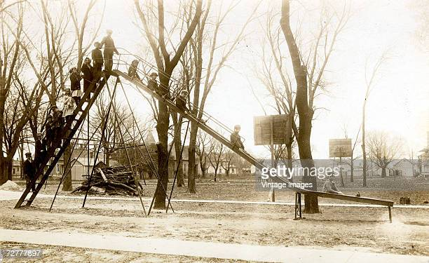 A group od children pose on a tall metal slide in a park early 20th century