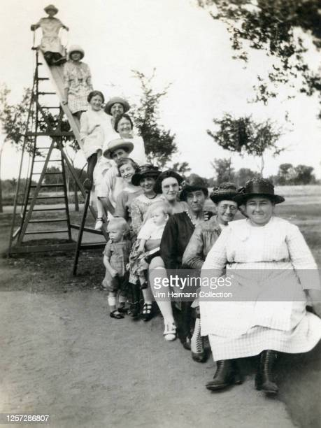 A group of 12 goodnatured women in dresses pose happily on a playground slide circa 1921