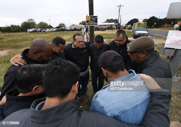 A group of 12 pastors from local churches pray beside a memorial service for victims of the mass shooting that killed 26 people in Sutherland Springs...