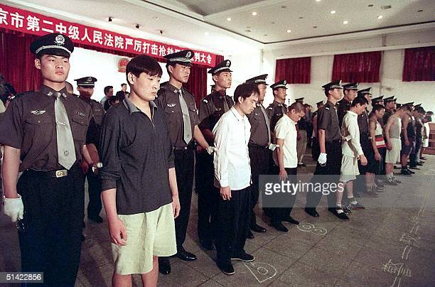 A group of 21 prisoners under police guard during a sentencing hearing at a court in Beijing 25 May 2001 where six were sentenced to death and the...