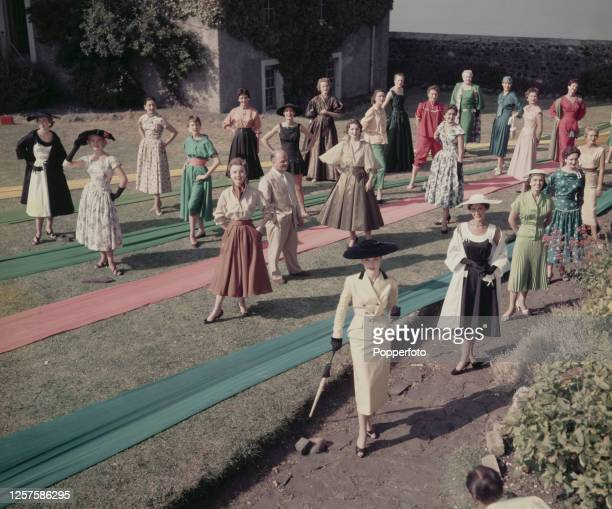 A group of 22 female fashion models pose wearing gowns made from the new taiho fabric created by textile manufacturer Cyril Lord standing in centre...