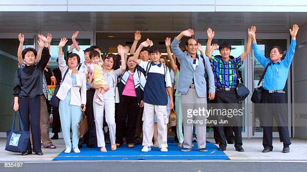 A group of 24 North Korean asylum seekers who had been hiding out on South Korean embassy grounds in Beijing wave as they arrive at Incheon...