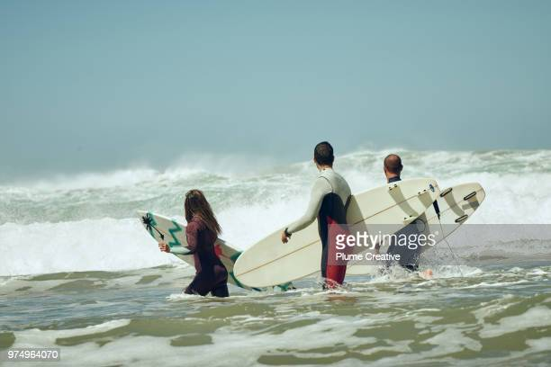 group of 3 surfers walking out of the surf with boards - atlantik stock-fotos und bilder
