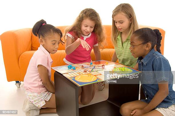 group of 4 young children sat around playing board games - game board stock photos and pictures