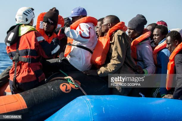 A group of 47 migrants is helped by a Sea Watch 3 crew member during their transfer from a rescued unflatable boat onto a Sea Watch 3 RHIB during a...