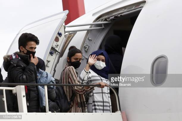 A group of 50 people including 16 asylumseeking minors and 34 migrants from overcrowded migrant camps many wearing protective face masks board a...