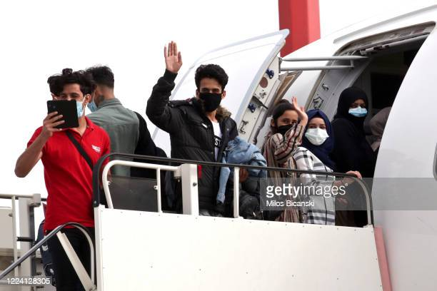 Group of 50 people, including 16 asylum-seeking minors and 34 migrants from overcrowded migrant camps, many wearing protective face masks, board a...