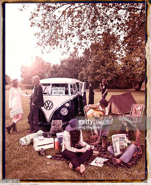 This image has been digitally manipulated A group of 60's styled hippies relaxing in the park alongside a vintage Volkswagen Type 2 camper van taken...