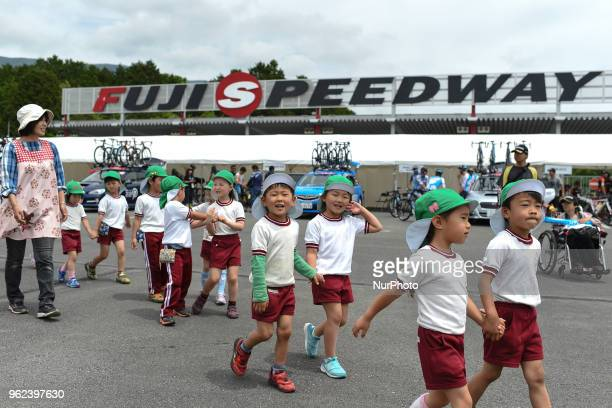 A group of a young school children passes near the main entrance to Fuji Speedway near the start of Fujisan stage the sixth stage of Tour of Japan...