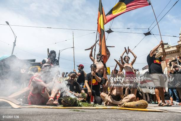 A group of Aboriginal men sitting in at an intersection waving Aboriginal flags and playing with traditional instruments during a protest by...