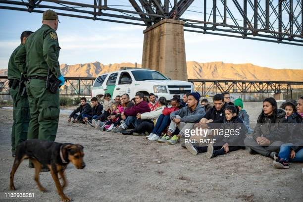 TOPSHOT A group of about 30 Brazilian migrants who had just crossed the border sit on the ground near US Border Patrol agents on the property of Jeff...