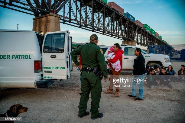 A group of about 30 Brazilian migrants who had just crossed the border get into a US Border Patrol van taking them off the property of Jeff Allen who...