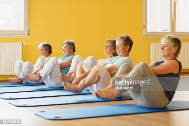 group of active senior women in yoga class exercising on mat