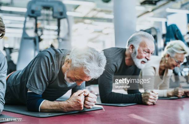group of active seniors exercising strength in plank position in a health club. - practicing stock pictures, royalty-free photos & images
