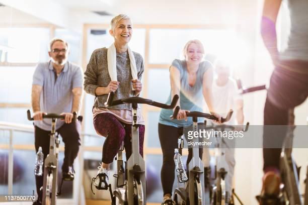 gruppe von aktiven senioren, die mit einem instruktor in einem fitnessstudio spinnunterricht haben. - fitnesseinrichtung stock-fotos und bilder