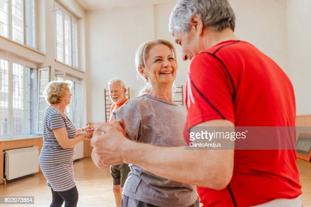 group of active seniors having fun dancing together - dance studio stock pictures, royalty-free photos & images
