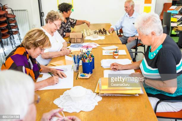 group of active seniors socializing at the activity center - community centre stock pictures, royalty-free photos & images
