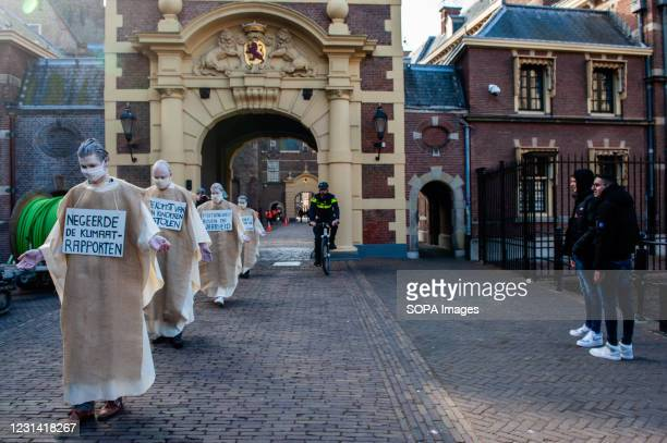 Group of activists dressed like penitents walk on the street during the demonstration. As a part of the Spring Rebellion campaign of Extinction...