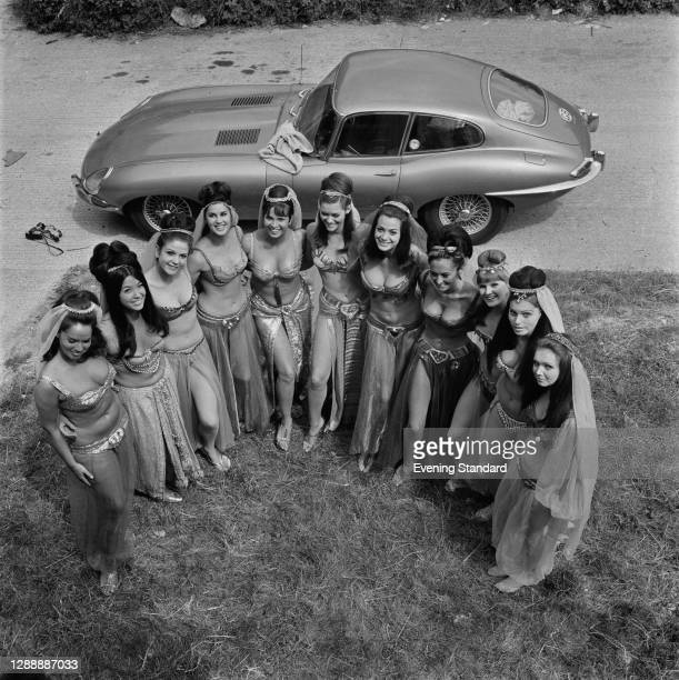 Group of actresses from the harem scene, posing with a Jaguar E-type on the set of the Carry On film 'Follow That Camel', UK, July 1967.