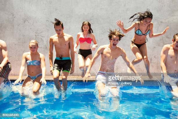 Group of adolecents hangni out and having fun in a swimming pool