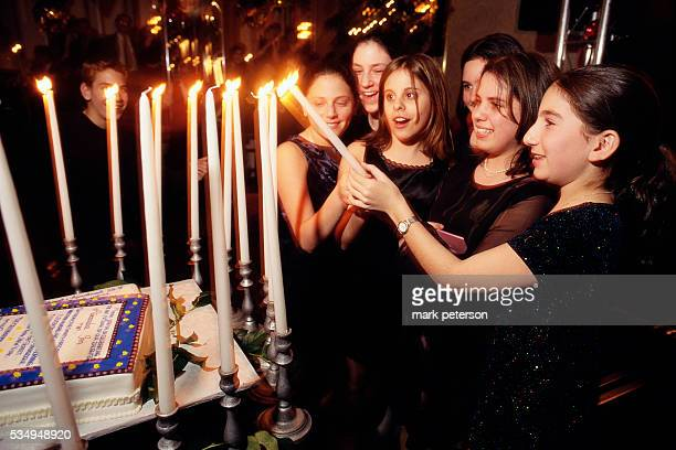 A group of adolescent girls helps their friend Ali Green light candles at her bat mitzvah celebration The reception takes place at a ballroom on...