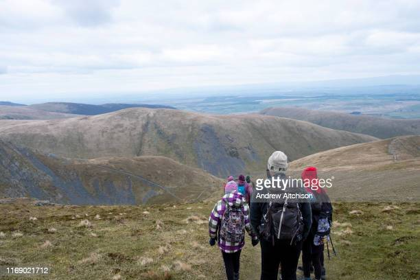 Group of adult and child hikers descend down a steep path from the summit of Blencathra Mountain, following the Scales Beck valley, Lake District,...