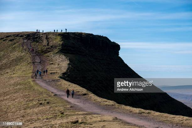 A group of adult and child ramblers walk along the dirt track along the summit of Pen Y Fan Mountain in Brecon Beacons National Park Wales Powys...