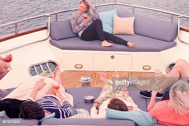 Group of adult friends enjoying a relaxing drink on board yacht