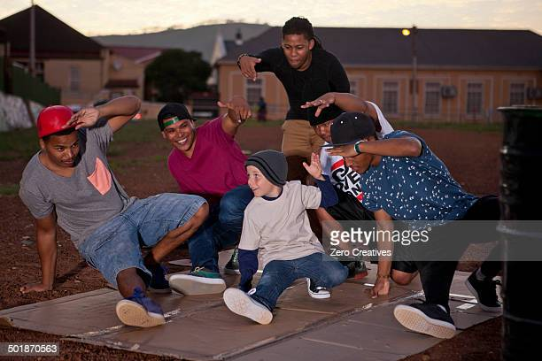 Group of adult males and boy breakdancing in park at dusk