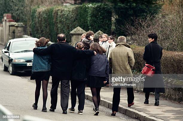 A group of adults and children embracing outside Dunblane primary school Scotland shortly after the shooting incident on the premises The Dunblane...