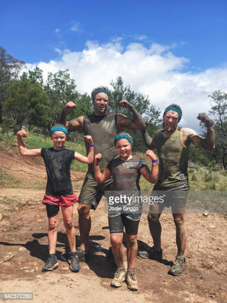 Group of adults and children flexing muscles during a mud run event