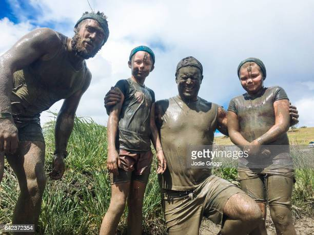 Group of adults and children standing together covered in mud during a mud run event