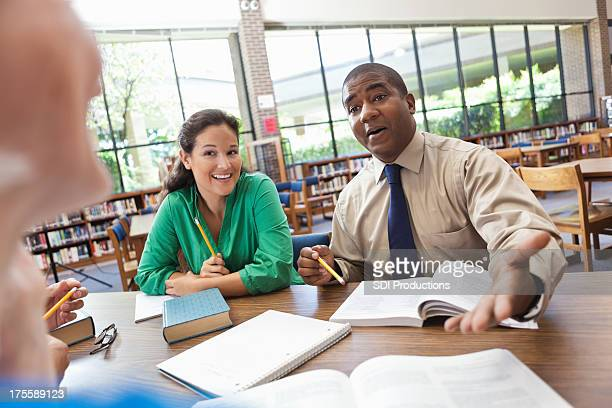 Group of adults continuing education studying together in library
