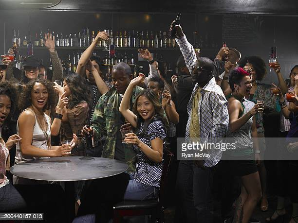 Group of adults drinking cocktails and cheering in club, arms raised