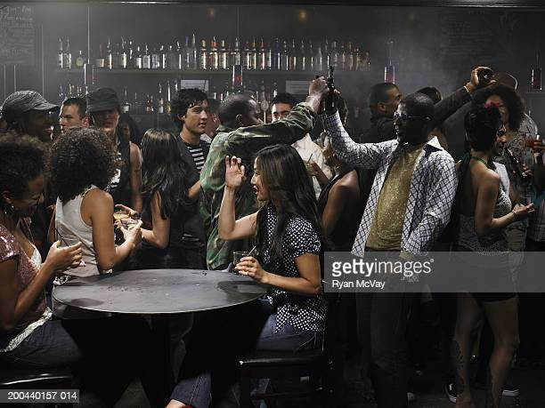 Group of adults drinking cocktails and talking in nightclub