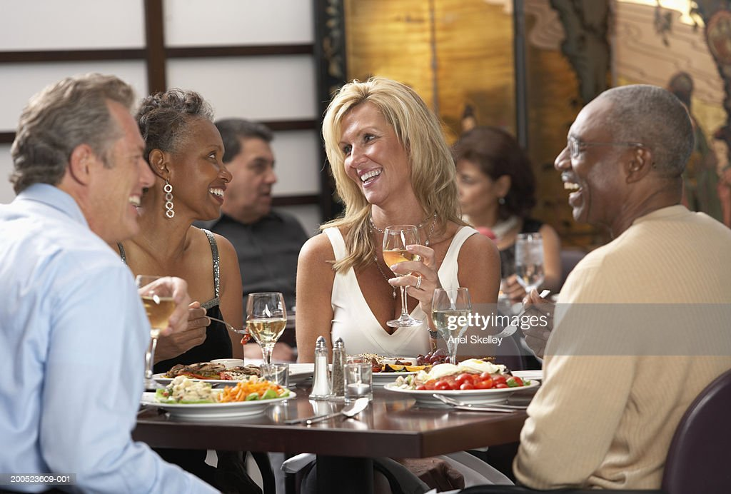 Group of adults eating in restaurant : Stock Photo