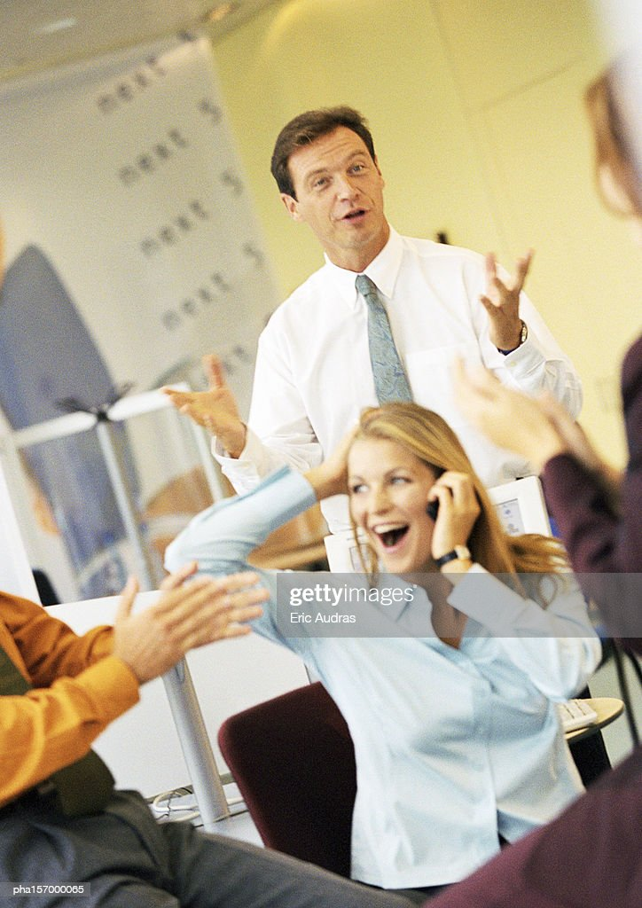 Group of adults in business attire, hands clapping, man standing with hands up, woman with mouth open and hand behind head : Stockfoto