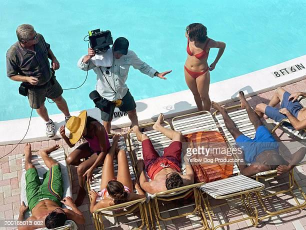 group of adults lying by poolside, film crew giving instructions - parte de uma série imagens e fotografias de stock