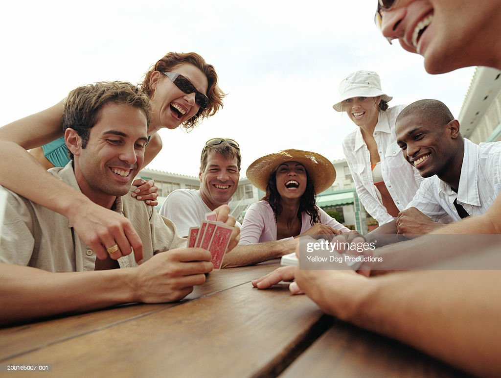 Group of adults playing cards by poolside of hotel : Stock Photo