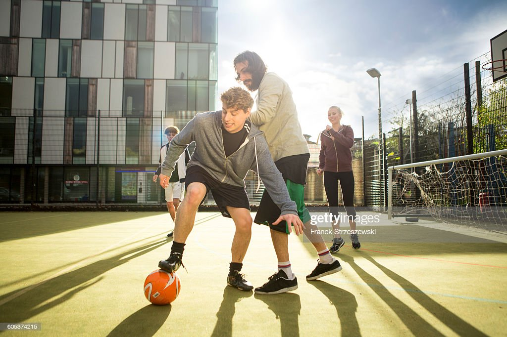 Group of adults playing football on urban football pitch : Stock Photo