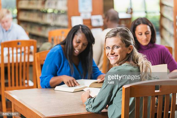 Group of adults reading books in library